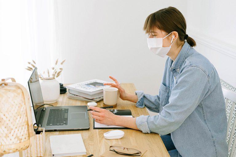 Bild einer jungen Frau mit Mundschutz während der Arbeit an Ihrem Schreibtisch